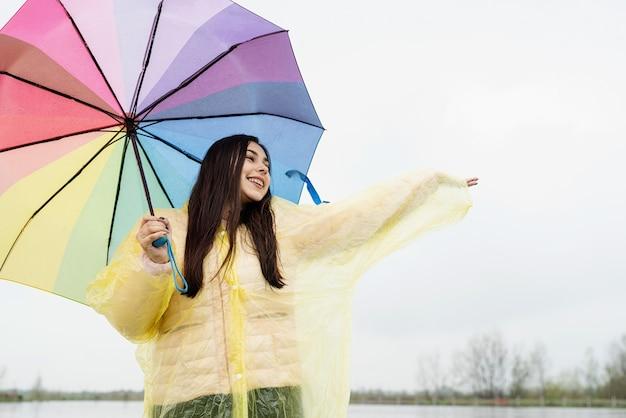 Mooie glimlachende brunette vrouw in gele regenjas met regenboogparaplu in de regen, regendruppels vangend met haar hand