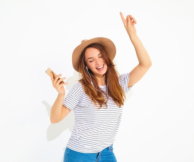 Mooie glimlachende brunette vrouw vrouw in casual hipster zomer kleding zonder make-up in bruine hoed luisteren muziek in telefoon met koptelefoon op wit wordt geïsoleerd