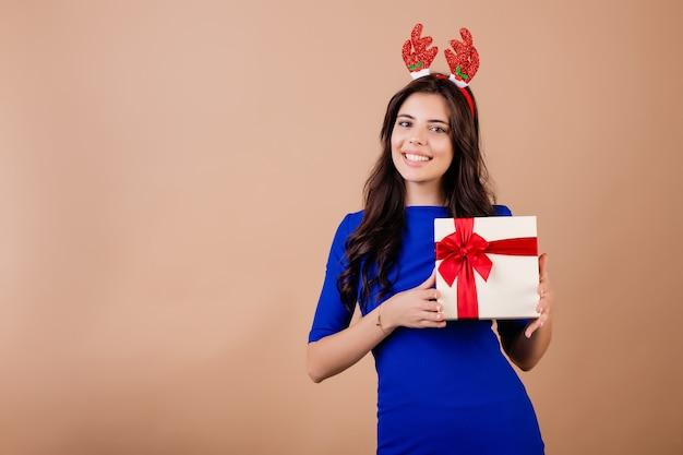 Mooie glimlachende de giftdoos van de vrouwenholding en het dragen van grappige die kerstmishoepel over bruin wordt geïsoleerd