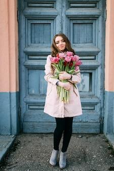 Mooie glimlachende donkerbruine vrouw die zich voor oude deur met een boeket van verse tulpen bevindt.