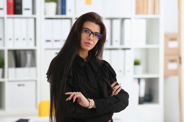 Mooie glimlachende donkerbruine vrouw in bureau