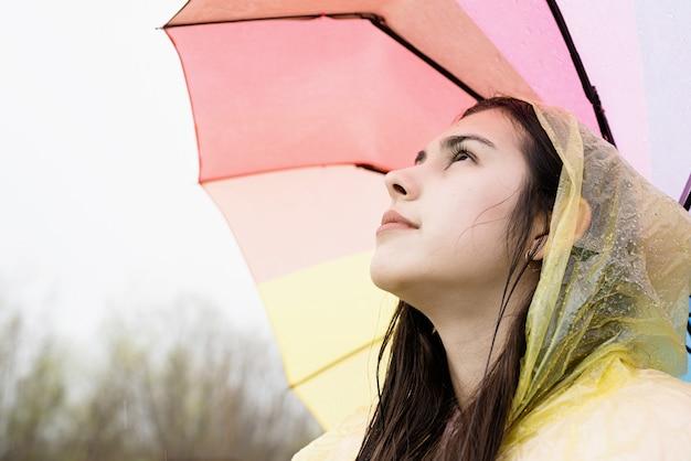 Mooie glimlachende donkerbruine vrouw in gele regenjas die regenboogparaplu in de regen houdt, wegkijkend. ruimte kopiëren