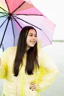 Mooie glimlachende donkerbruine vrouw in gele regenjas die regenboogparaplu in de regen houdt