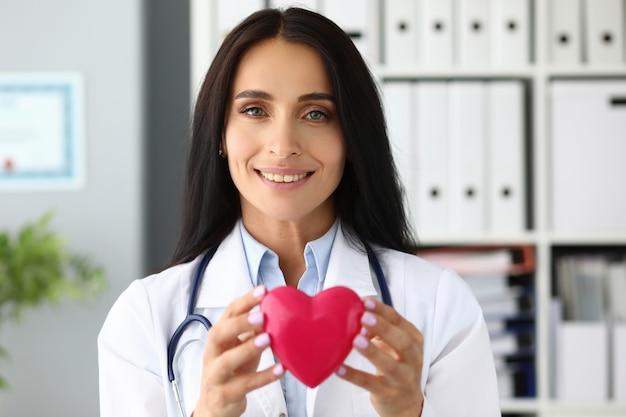 Mooie glimlachende gp-holding in handen rood stuk speelgoed hart