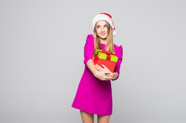 Mooie glimlachende grappige gelukkige dame in korte roze jurk en nieuwjaarshoed houden kartonnen doos verrassing in haar handen