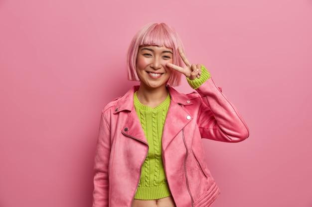 Mooie glimlachende jonge aziatische vrouw met roze haar maakt v-teken voor vrede, toont twee vingers over oog