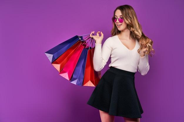 Mooie glimlachende jonge blonde vrouw in zonnebril met boodschappentassen en creditcard op een roze muur