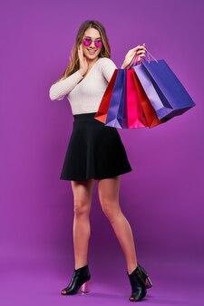 Mooie glimlachende jonge blonde vrouw in zonnebril met boodschappentassen op een roze muur