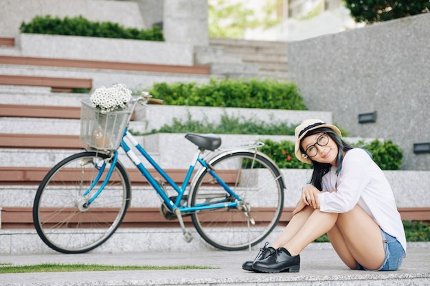 Mooie glimlachende jonge chiense-vrouw in denimborrels die op grond ext aan haar fiets zitten en camera bekijken