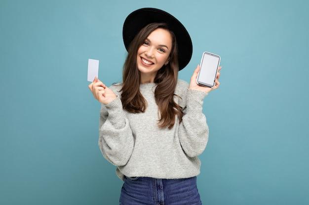 Mooie glimlachende jonge donkerbruine vrouw die zwarte hoed en grijze sweater draagt die over blauw wordt geïsoleerd