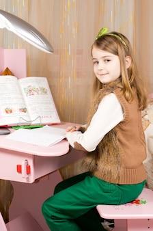 Mooie glimlachende jonge meisjeszitting die bij haar roze bureau in haar slaapkamer werken die haar huiswerk voor school doet
