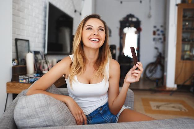 Mooie glimlachende jonge vrouw die beet van chocolade eet