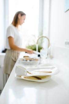 Mooie glimlachende jonge vrouw die de schotels in moderne witte keuken wast.