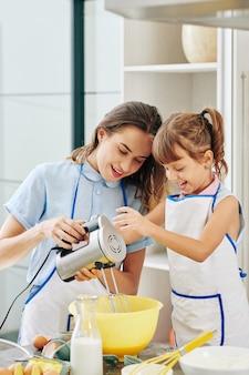 Mooie glimlachende jonge vrouw die dochter toont hoe eieren met elektrische mixer te kloppen