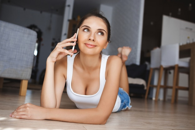 Mooie glimlachende jonge vrouw die op telefoon spreekt die bij de vloer in de woonkamer bepaalt