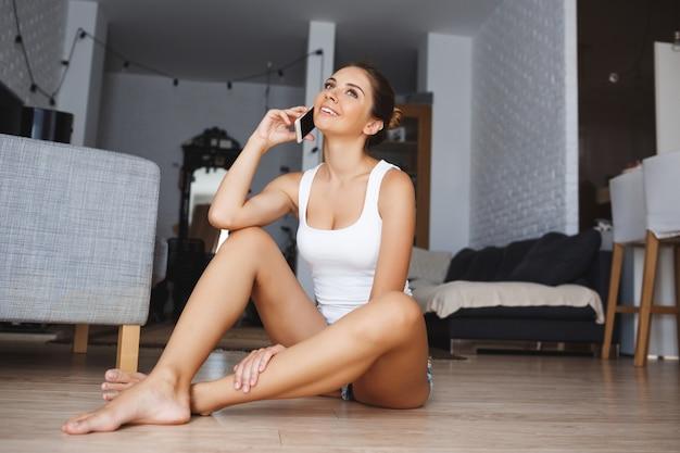 Mooie glimlachende jonge vrouw die op telefoonzitting met de benen over elkaar bij de vloer in woonkamer spreken