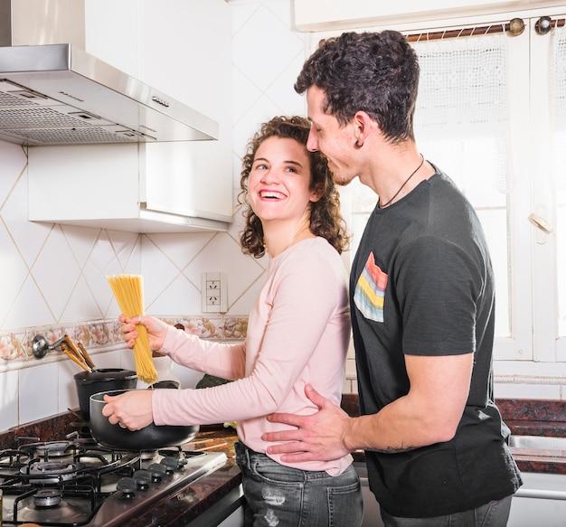 Mooie glimlachende jonge vrouw die spaghetti voorbereidt die haar echtgenoot bekijkt