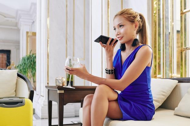Mooie glimlachende jonge vrouw glas wijn drinken in de lobby van het hotel en spraakbericht opnemen voor vriend