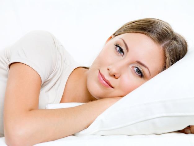 Mooie glimlachende jonge vrouw heeft een rust op het bed
