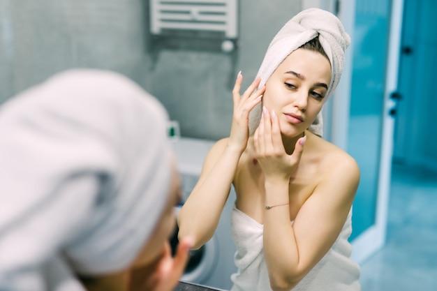 Mooie glimlachende jonge vrouw in badjas en handdoek op hoofd die spiegel in badkamers bekijken
