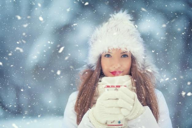 Mooie glimlachende jonge vrouw in warme kleding met kop hete theekoffie of punch