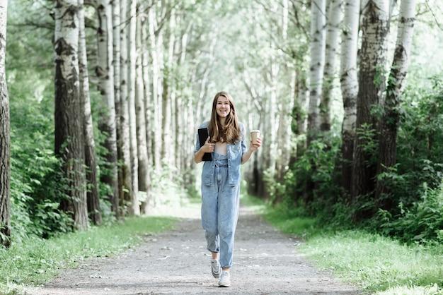 Mooie glimlachende jonge vrouw loopt in het park met een laptop en koffie