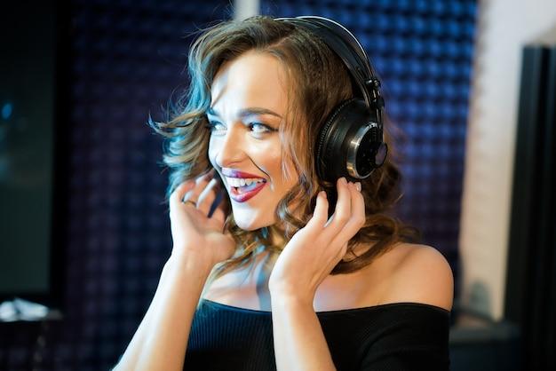 Mooie glimlachende jonge vrouw met golvend haar wat betreft hoofdtelefoons
