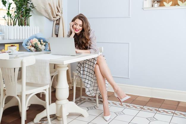 Mooie glimlachende jonge vrouw met lang krullend haar die zit en laptop gebruikt in café