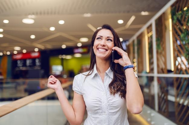 Mooie glimlachende kaukasische brunette in overhemd dat zich binnen en over slimme telefoon spreekt bevindt. winkelcentrum interieur.