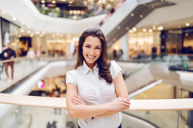 Mooie glimlachende kaukasische brunette in overhemd dat zich in winkelcomplex met gekruiste wapens bevindt.
