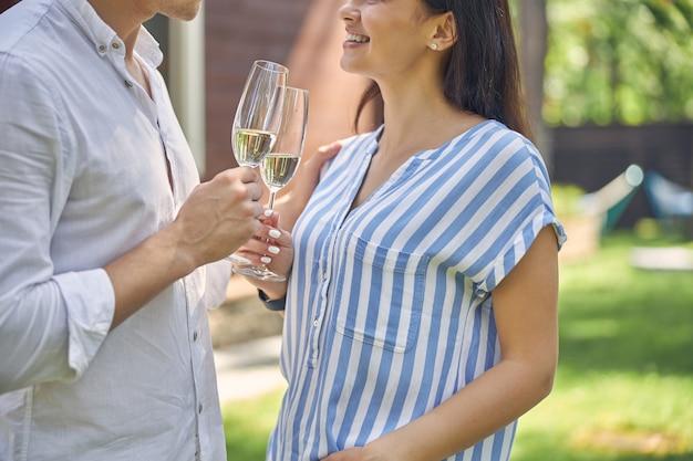 Mooie glimlachende man en vrouw die samen praten terwijl ze koude champagne drinken