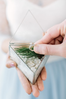Mooie glimlachende meester van de ceremonie van het huwelijk met glazen doos met trouwringen