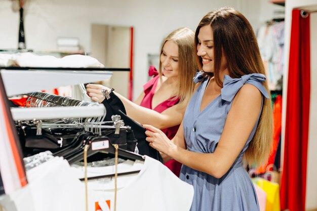 Mooie, glimlachende meisjes die kleren kiezen en kopen