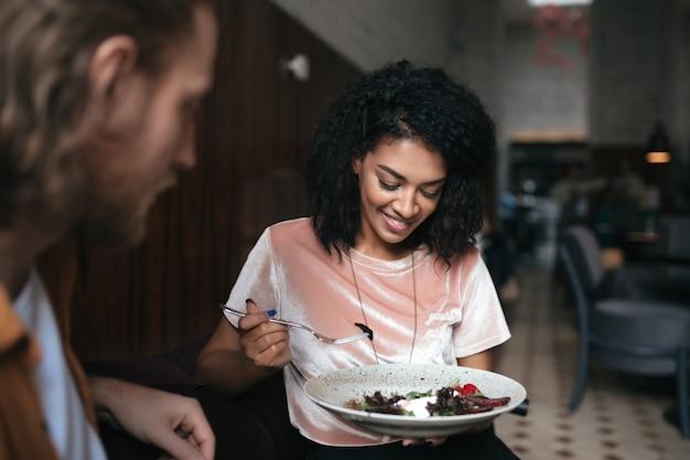 Mooie glimlachende meisjeszitting in restaurant met vriend. vrij afrikaanse amerikaanse dame zit in café met salade in de hand