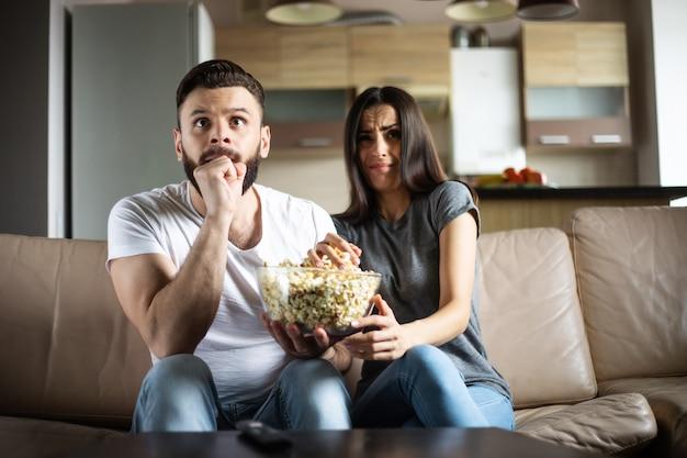 Mooie glimlachende moderne verliefde paar kijkt naar een film of film op tv terwijl ze ontspannen op de bank in hun eigen appartement