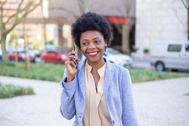 Mooie glimlachende onderneemster die op telefoon op straat spreekt