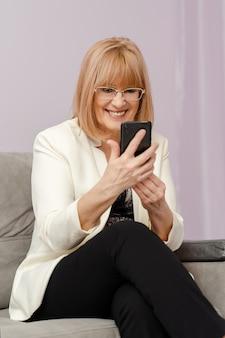 Mooie glimlachende rijpe vrouw die op videogesprek spreekt