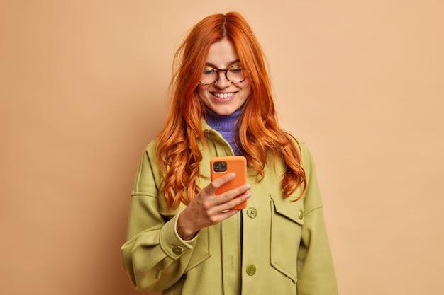 Mooie glimlachende roodharige vrouw gebruikt mobiele telefoontoepassing blij om bericht van vriendje heeft een prettig gesprek online, gekleed in modieuze herfstkleren.