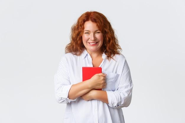 Mooie glimlachende roodharige vrouw van middelbare leeftijd die blij en tevreden kijkt, rode notitieboekplanner met vrolijke uitdrukking vasthoudt, plannen maakt, aantekeningen maakt, online cursus begint, witte muur.