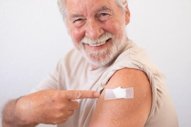 Mooie glimlachende senior man 70 na ontvangst van het coronavirus covid-19-vaccin.