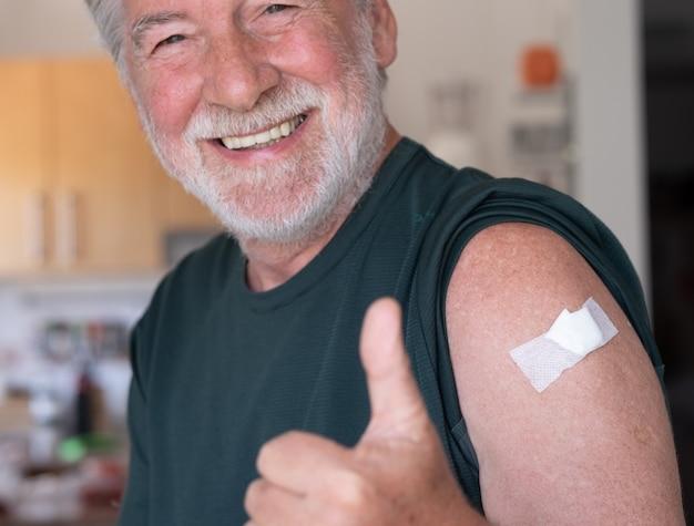 Mooie glimlachende senior mannelijke 70 na ontvangst van het coronavirus covid-19-vaccin. positieve bebaarde man met duim omhoog