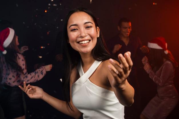 Mooie glimlachende vrouw die bij nieuwe jarenpartij danst