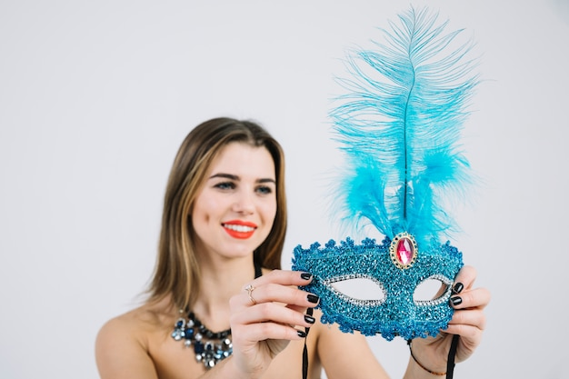 Mooie glimlachende vrouw die blauw maskerade verfraaid carnaval masker bekijkt