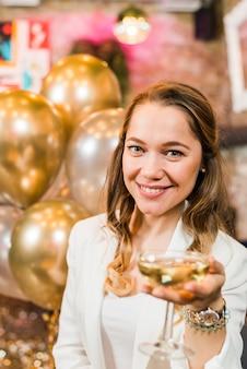 Mooie glimlachende vrouw die een glas whisky aanbiedt