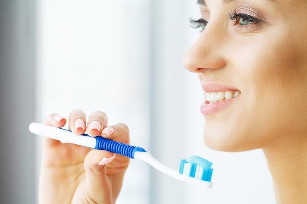 Mooie glimlachende vrouw die gezonde witte tanden met borstel borstelt