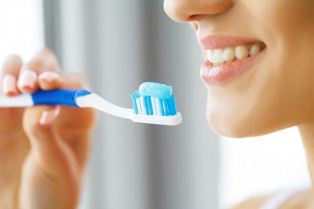 Mooie glimlachende vrouw die gezonde witte tanden met borstel borstelt.
