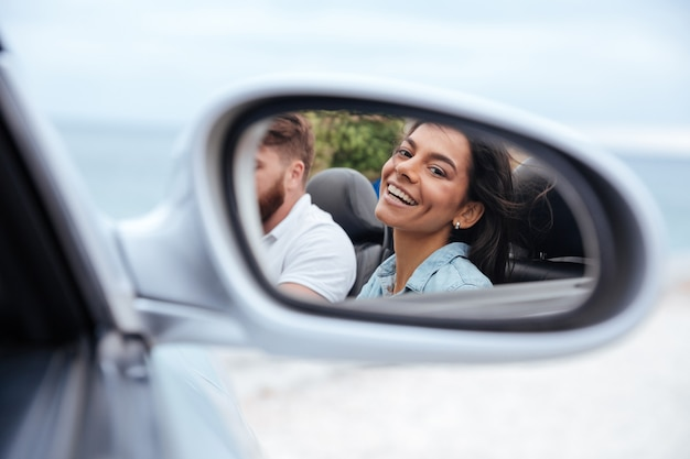 Mooie glimlachende vrouw die haar gedachtengang in een autospiegel bekijkt