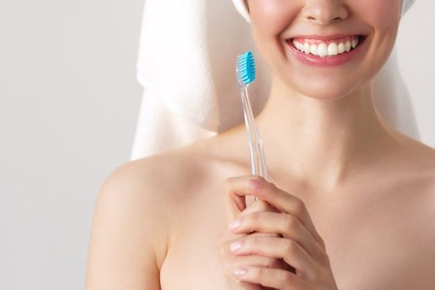 Mooie glimlachende vrouw die haar tanden met een tandenborstel in een mondhygiëneconcept schoonmaakt. geïsoleerd op wit. Premium Foto