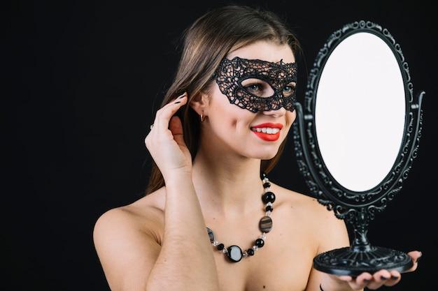 Mooie glimlachende vrouw die in carnaval masker in hand spiegel kijkt
