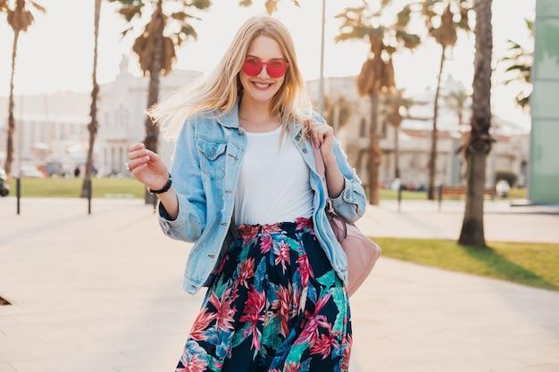 Mooie glimlachende vrouw die in de straat van de stad loopt in een stijlvolle bedrukte rok en een oversized denim jasje met een roze zonnebril